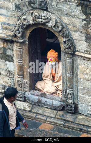Nepalese man passing in front of an Hinduist Sadhu seated in a shrine, Holy Man, Pashupatinath Temple, Kathmandu, - Stock Photo