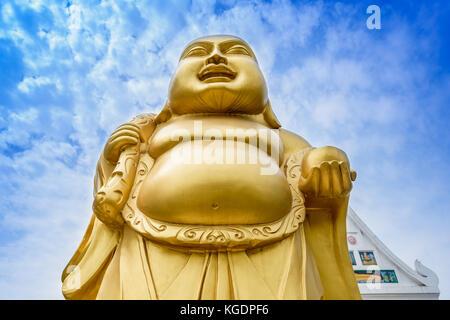 Laughing Buddha statue at a Buddhist monastery at Sarnath, Varanasi, India. - Stock Photo