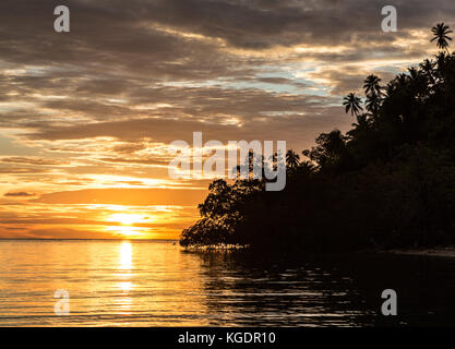 Stunning sunset in the Togian (or Togean) islands in Sulawesi, a remote corner of Indonesia still untouched by pollution - Stock Photo