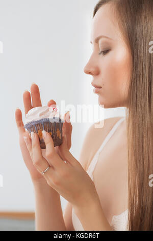 Woman wants to eat a cupcake - Stock Photo