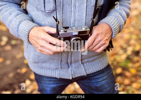 Senior man on a walk in autumn forest. - Stock Photo