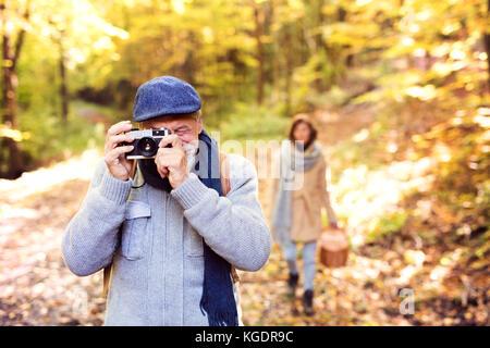Senior couple on a walk in autumn forest. - Stock Photo