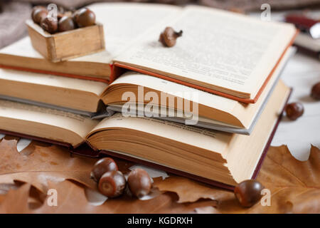 stack of books on the table with a red tablecloth. an open book with curled leaves laying on top. love of books. - Stock Photo