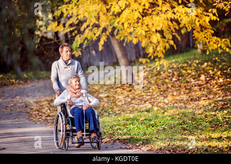 Senior man and woman in wheelchair in autumn nature. - Stock Photo