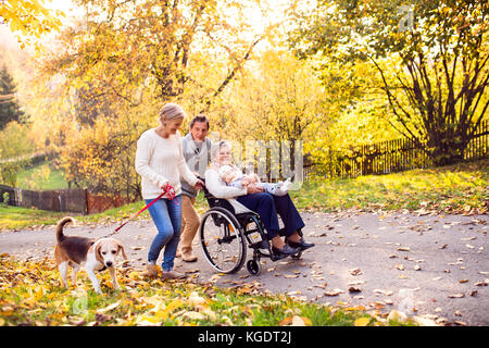 Extended family with dog on a walk in autumn nature. - Stock Photo