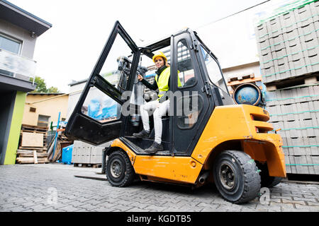Female forklift truck driver outside a warehouse. - Stock Photo