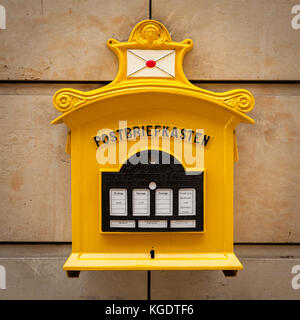 An old vintage yellow mailbox in Dresden Germany with inscription 'Mailbox' - Stock Photo