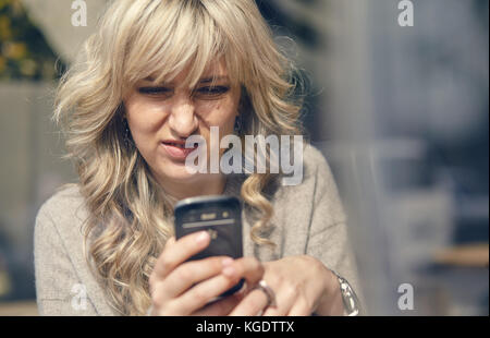 A woman sees something unpleasant on the phone - Stock Photo