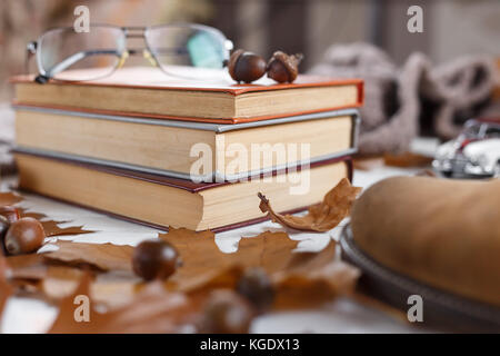 Stack of books on the table with eyeglasses laying on top. Education concept - Stock Photo