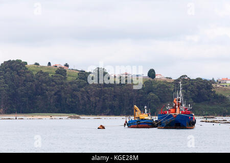two boats anchored at the entrance of a small port - Stock Photo