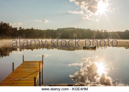 The mid-July early morning cooler air creates a light fog over Patricia Lake in northern Wisconsin. - Stock Photo