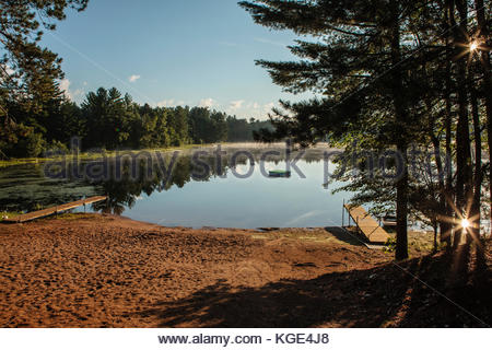 The mid-July early morning cooler air creates a light fog over Patricia Lake in northern Wisconsin, as the sun reflects - Stock Photo