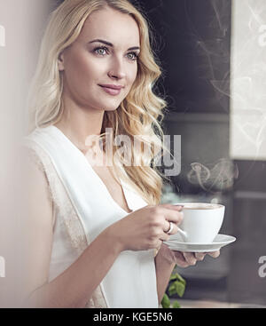 Portrait of a pretty blond lady drinking a cup of coffee - Stock Photo