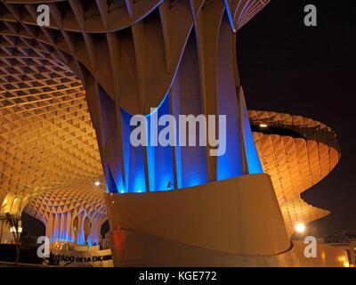 blue and gold night time illumination at base of Metropol Parasol 'The Mushroom' Seville, Spain - Stock Photo