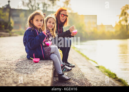 Family eating ice cream, sitting on banks of river Ljubljanica. Mother and twin daughters are sitting next to a - Stock Photo