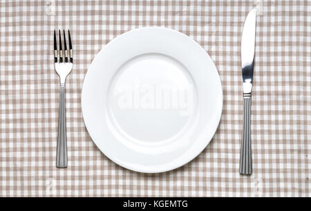 Empty white plate with fork and knife on checked gingham tablecloth - Stock Photo