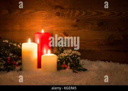 Christmas candles with Holly and conifer branches on an artificial snow and wooden background. - Stock Photo
