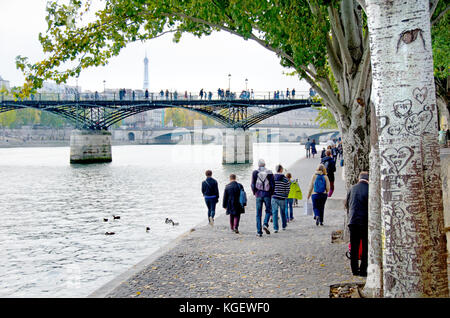 Paris, France. People walking along the north bank of the River Seine, Pont des Arts and Eiffel Tower behind - Stock Photo