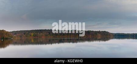 Large Panorama of Tree Line Around Large Lake in Fall Season - Stock Photo