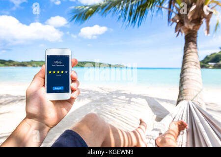 Customer review online app on smartphone screen asking user on the beach to rate experience and give feedback, satisfaction - Stock Photo