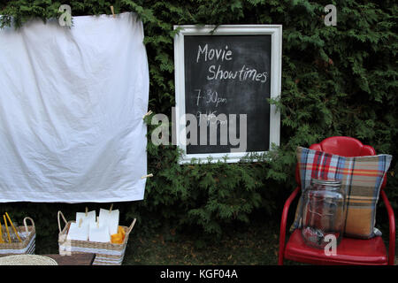 Set up for watching a movie outdoors with food and chairs - Stock Photo