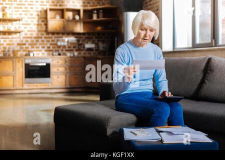 Cheerless elderly woman making calculations - Stock Photo