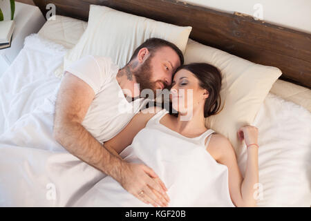 man wakes a woman in the bedroom in the morning weekend - Stock Photo