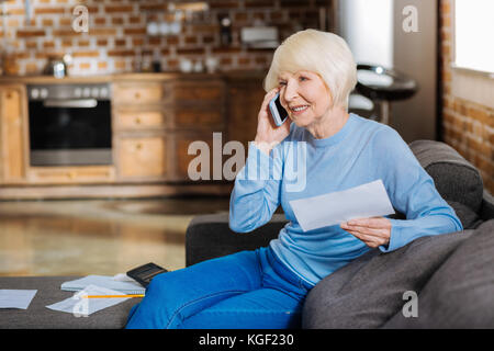 Nice aged woman making a call - Stock Photo