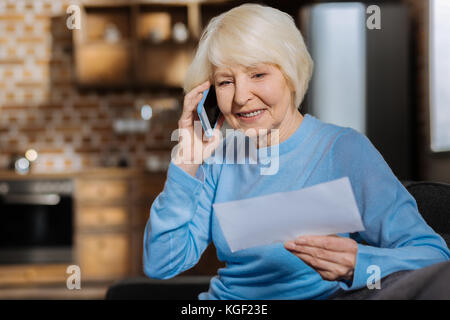 Delighted elderly woman making a phone call - Stock Photo