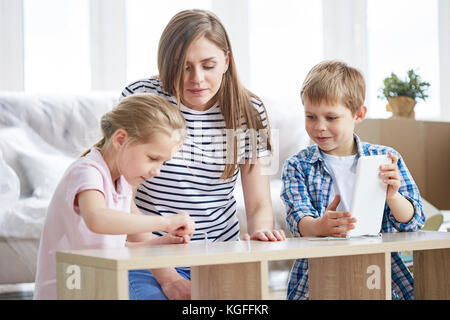 Attractive young mother and her cute children enjoying each others company while gathered together in living room - Stock Photo