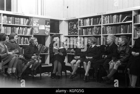 1955, historical picture shows a female teacher sitting and reading a story to a small group of young children in - Stock Photo