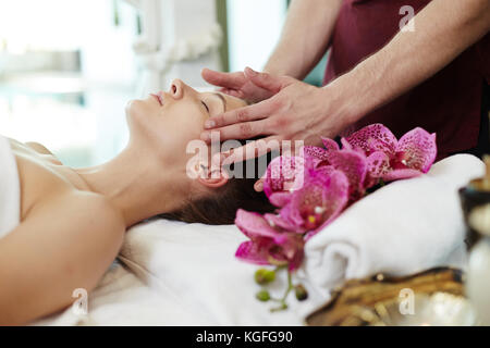 Side view portrait of beautiful young woman enjoying face lifting massage lying on table in SPA center and relaxing - Stock Photo