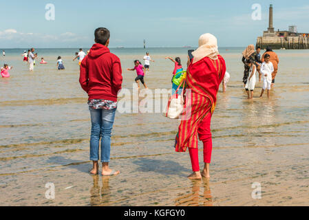 Asian families enjoying a day on the beach at Margate, Kent. - Stock Photo