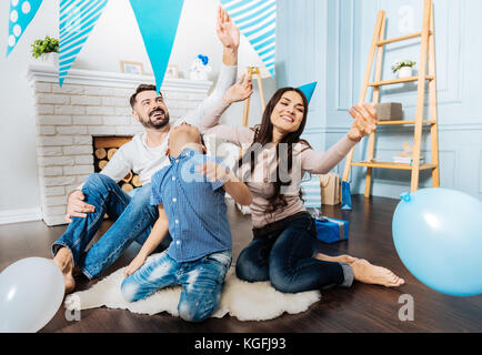 Cheerful family playing with balloons in the living room - Stock Photo