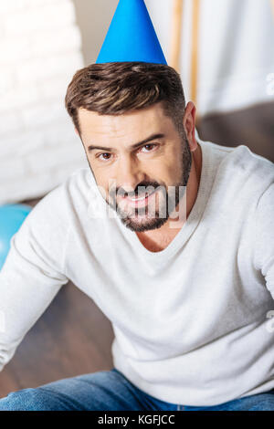 Top view of handsome young man in party hat - Stock Photo