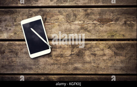 Rustic wooden table with smartphone. View from above with copy space - Stock Photo