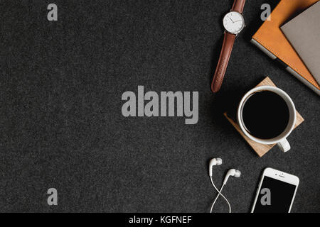 Styled stock minimalist aerial photo of a iPhone, headphones, notebooks, watch and coffee plus room for adding text - Stock Photo