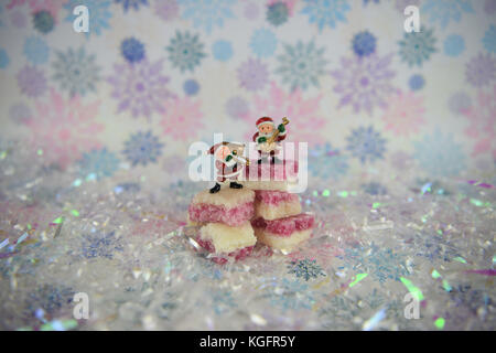 Christmas food photography picture of old fashioned English white pink coconut ice sugar sweets with glitter snowflake - Stock Photo