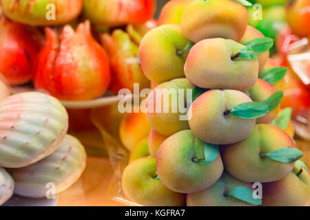 Cakes with marzipan in the form of peach. - Stock Photo