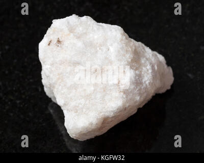 macro shooting of natural mineral rock specimen - rough anhydrite stone on dark granite background from Adygea, - Stock Photo