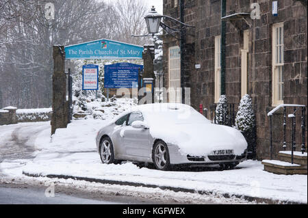 Cold, snowy winter day with snow-covered car parked outside stone cottages & church gate in village - Burley-in - Stock Photo