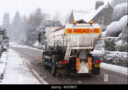 Cold, snowy winter scene as gritter lorry with snow plough, drives, spreading grit & clearing deserted road - Hawksworth, - Stock Photo