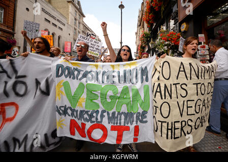 Vegan activists shouting and chanting while marching in Whitehall London during an animal rights protest demonstration - Stock Photo