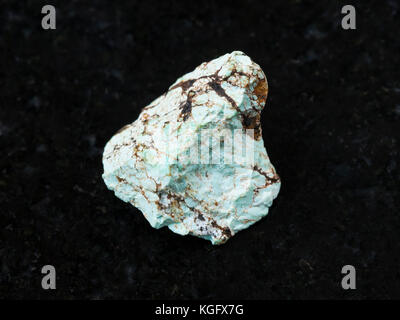 macro shooting of natural mineral rock specimen - raw green Turquoise gemstone on dark granite background - Stock Photo