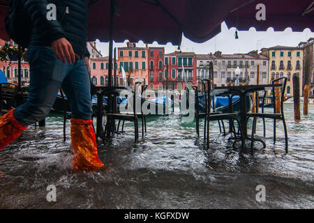 Venice, Italy. 07th November, 2017.  A tourist walks in the water along the Grand Canal next to Rialto bridge during - Stock Photo