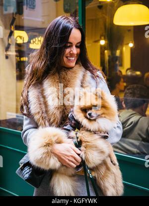 Portrait of woman smiling in fur coat, holding Pomeranian dog - Stock Photo