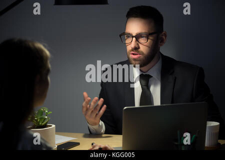 Male boss in suit explains to female employee project ideas and plans in late evening meeting still at workplace. - Stock Photo