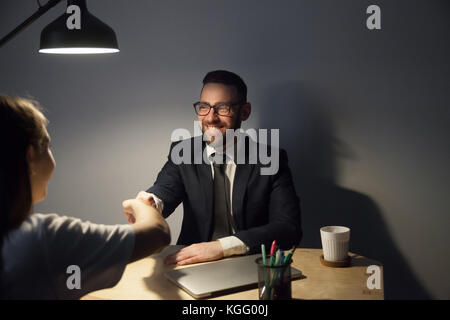 Two businesspeople seal a deal with handshake after long negotiations in dark office with lamp light. Smiling bearded - Stock Photo