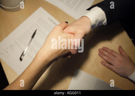 Business handshake. Close up top view of two businesspeople shaking hands after signing contract. Human resources - Stock Photo