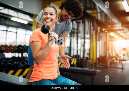 Young beautiful woman doing exercises with personal trainer - Stock Photo